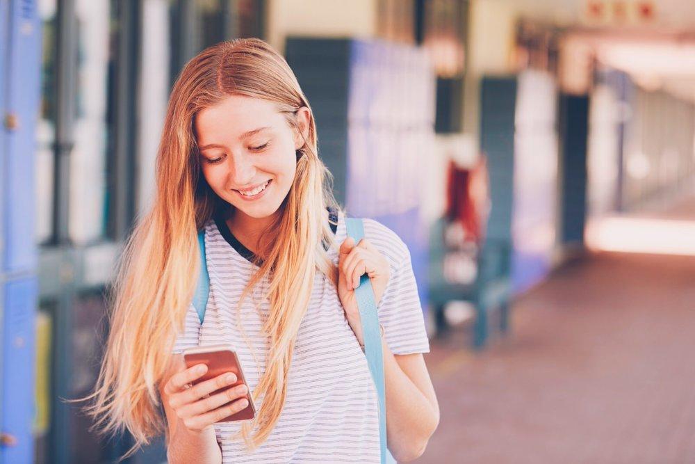 happy-teenage-girl-using-smartphone-in-school-PJT7HVC (Priime Amplify)-1.jpg