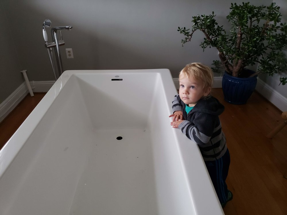 Toddler contemplates life as a tub model