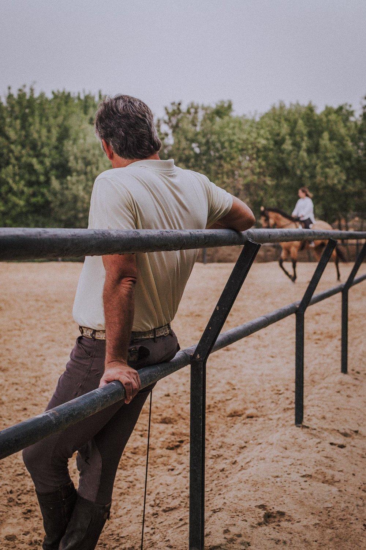 """10.00  / Dagens andre undervisningstime. Alfonso lener seg på gjerdet som rammer inn dressurbanen og betrakter Nadador under en annen rytter enn seg selv. Han har vært en """"very naughty horse"""" de siste ukene. Nå skal Alfonso knekke koden med han på nytt før han setter kunder opp på ham igjen."""