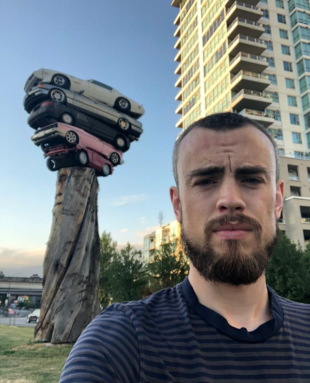 The 2018-2020 Vancouver Biennale will create a lasting impact across the city. As a member of the VBYA, I am excited to see public art brought to unique locations throughout Vancouver. I am digital marketer by trade, with a focus on e-commerce. . Title: Trans Am Totem Artist: Marcus Bowcott (b. 1951, Canada) Medium: Five refinished cars, cedar tree, metal column, solar panel, lights Dimensions (H x W x D): 10 x 5.2 x 2 m (33 feet x 17 feet x 6 feet 7 inches) Weight: 11,340 kg (25,000 lbs) Location: Quebec Street and Milross Avenue in Vancouver . By stacking smashed automobiles and levitating them high above the roadway, Bowcott serves to remind us of the ultimate responsibilities we bear to our planet and future generations. Trans Am Totem fantasizes a justified end to car culture even as countless automobiles zoom past on asphalt and concrete ribbons and ooze pollutants and spent carbon fuels into the atmosphere. The artist's vision of Nature triumphant subversively reminds us ultimately of our ongoing contributions to global warming and further environmental degradation. . #VanBiennale #VBYA #VanBiennaleYA #reimagen #publicart  #yvrart