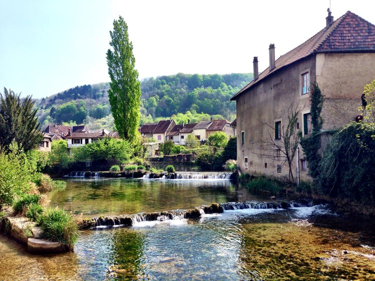 Arbois, the Jura. The River Cuisance flows past 16th-century stone buildings some with 12th century cellars.