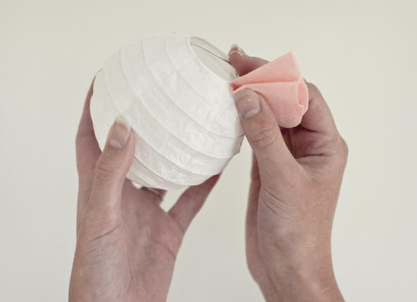 A woman Folding the circle in half and put a little hot glue on the center, then fold over to secure