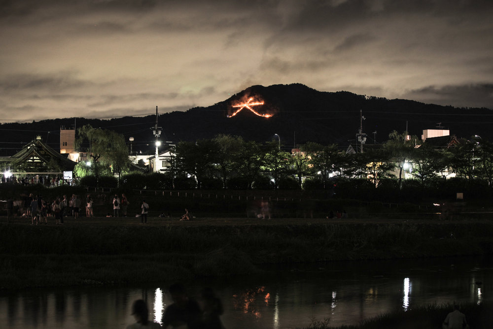 How Daimonjiyama looks on August 16 from the Kamo River Delta. The character Dai 大, stretches 160 metres across the face of the mountain. The tradition of setting fires to send off the spirits started in 1489, when Abbot Osen Keisan lit the character to send off Shogun Ashikaga Yoshimasa's son, who had died of an illness aged 25.