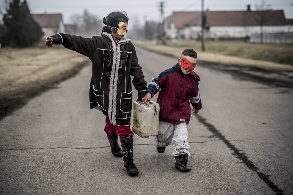 Their house has no running water, so they fetch water from the nearby well. Here Virág and Szabi are carrying a ten litre jerrican from the well, wearing the carnival masks they have made in school, or nursery school.