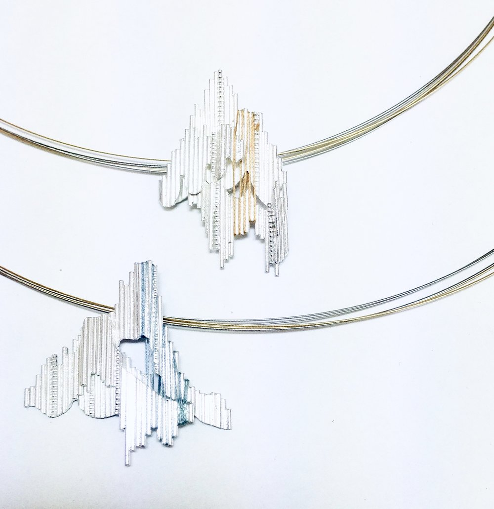 "Follow the Thread - Necklaces made for the Dazzle exhibition, ""Follow the Thread"". Exhibition at the Dovecot Studios Edinburgh, 2013.Two Silver necklaces, with silk threads, steel neck wire with 18ct Gold Plating. The design depicts a fragmented landscape, with threads weaving through the linear structure to highlight the depth of form."