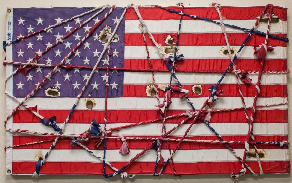"Leave No Man Behind, 2018. Mixed Media intertwined and knotted over American flag. 37 x 61""."