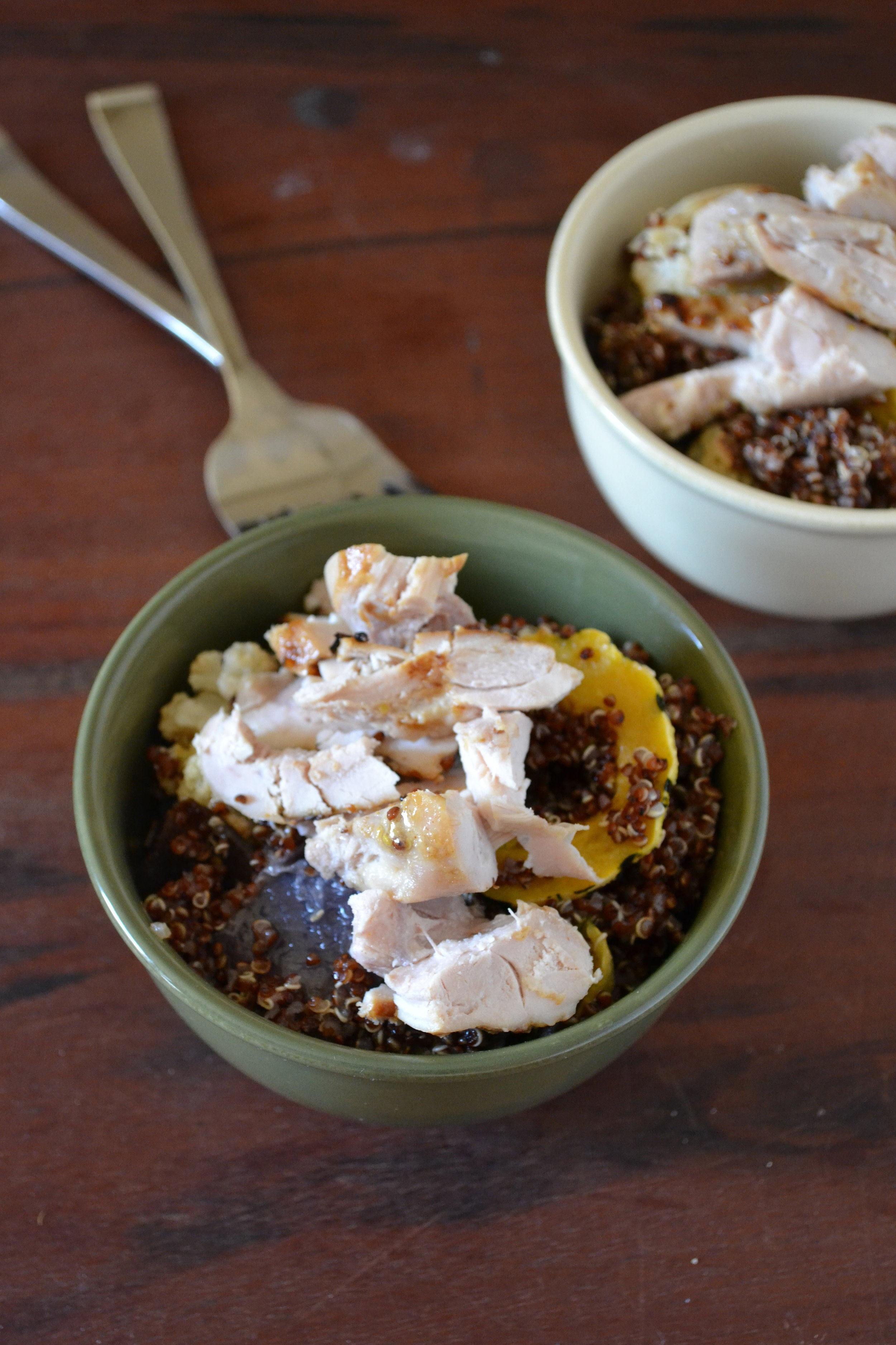 a bowl of red quinoa & veggies topped with chicken