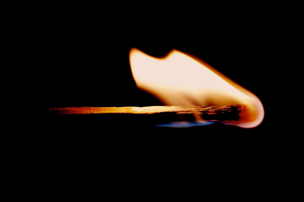 An image of a burning match against a black background.