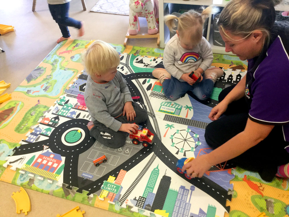 Childcare staff playing cars