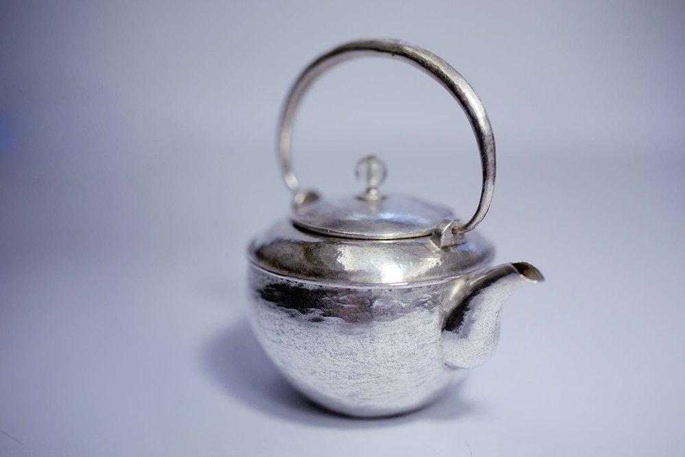 「太虚」:壶身保留手工缎打过程的敲痕,并以一弦纹的设计象徵柔中带刚的含义,壶嘴的造型似鸽子肚,出汤时能够有美丽平顺的优雅线条。