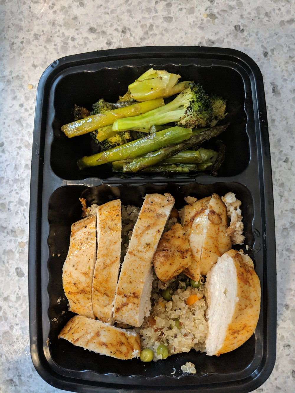 Individually-portioned spicy chicken and veggie quinoa meal with a side of roasted asparagus and broccoli
