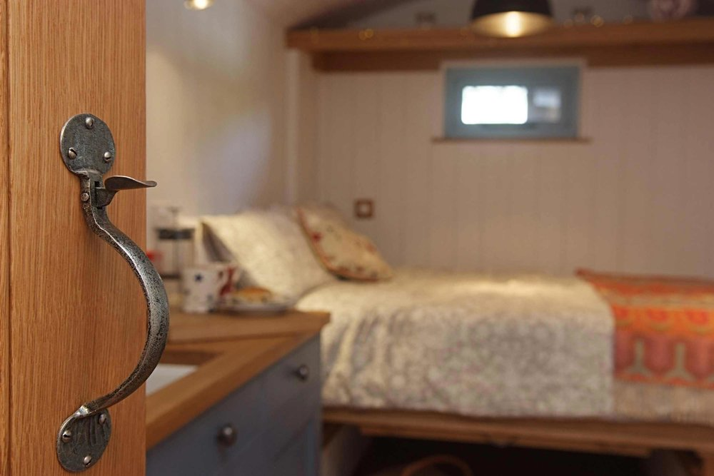 Interior of Shepherds Hut showing the pull down double bed, hand built door and hand forged iron door latches