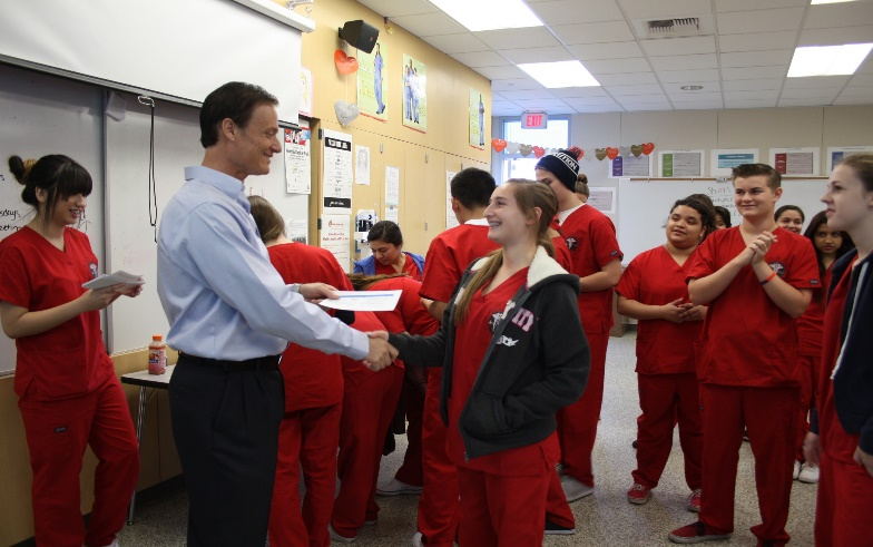 Student inspiring to become a Nurse Practitioner is receiving her American Heart Association HeartSaver CPR/Automated External Defibrillator Course Completion Card from the Heart2Heart Foundations Founder and Chief Executive Officer Richard DeRose.