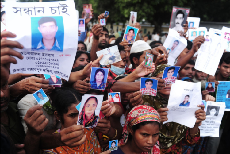 Bangladeshi relatives hold photos of missing and dead workers. AFP/Getty Images