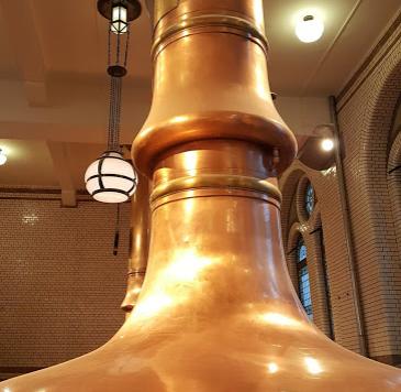 """Figura 13.    En Heineken Experience (Ámsterdam, Países Bajos) están en exhibición algunos de los equipos de elaboración que alguna vez se usaron en la famosa cervecería. Esta paila de cocción (""""Wortketel"""" en holandés) tiene un anillo que asegura la remoción de compuestos no deseados al evitar que los vapores que se condensaron a lo largo del tubo regresen al mosto."""