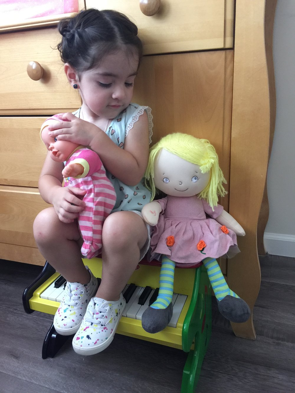 Playing with one of her many dolls