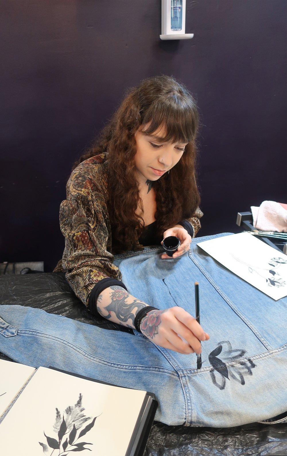 Artist Alba Rey handpainting on denim.jpeg