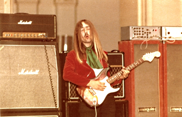 "Close-up from the same show, showing what was to become Uli's main amp on the far left - a Marshall 100W Super Lead tremolo - Later nicknamed ""the Beast"" for its enormous power, which it combines with a clean, but singing tone.  Uli played this amp on virtually every single album from  Fly To The Rainbow  in 1974 onwards, up to and including  Scorpions Revisited  in 2013. Occasionally ""The Beast"" will still grace the stage.  The Marshall Superlead was designed by Ken Bran for Jimi Hendrix in the late Sixties and is still Uli's favourite Marshall amp.  Today Uli tends to play Blackstar Artisan Amps, which are more reliable for touring and which are somewhat modeled on the Plexis. Behind Uli can be seen one of two Vox AC30 amps, which were his favourites before the arrival of the Marshall Plexi Amp."