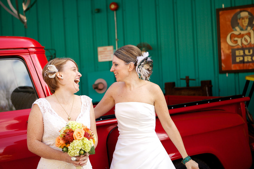 Two brides laughing at their gay wedding