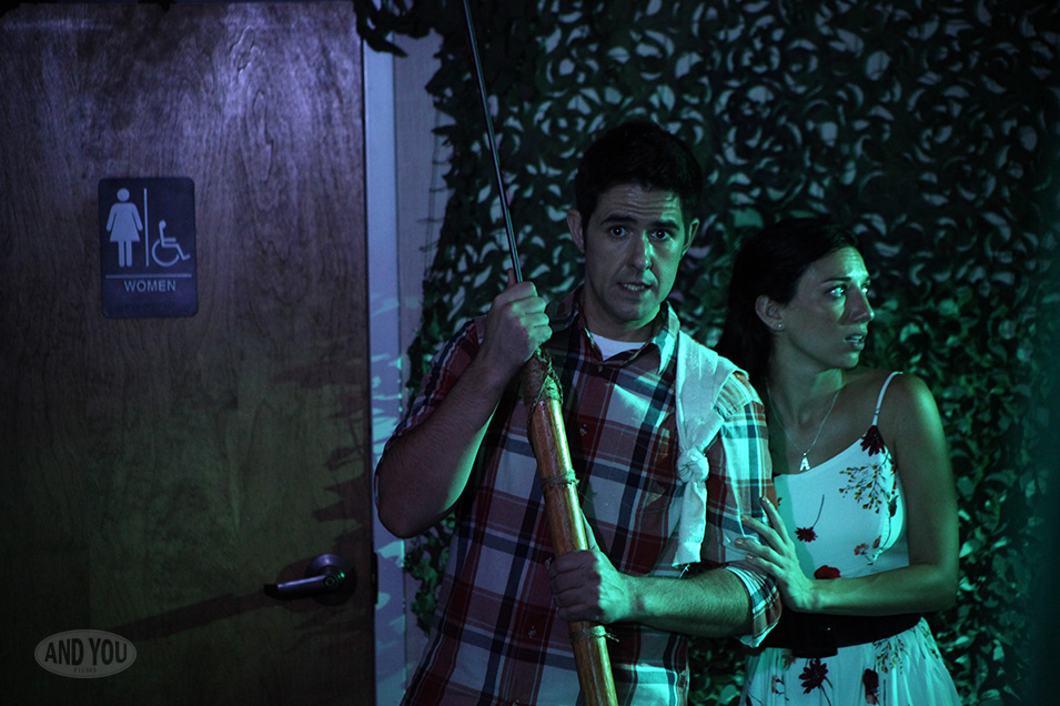 Andy Gion and Aléa Figueroa as Charley and Annie, stand tense in front of a women's restroom. He holds a harpoon for some reason.