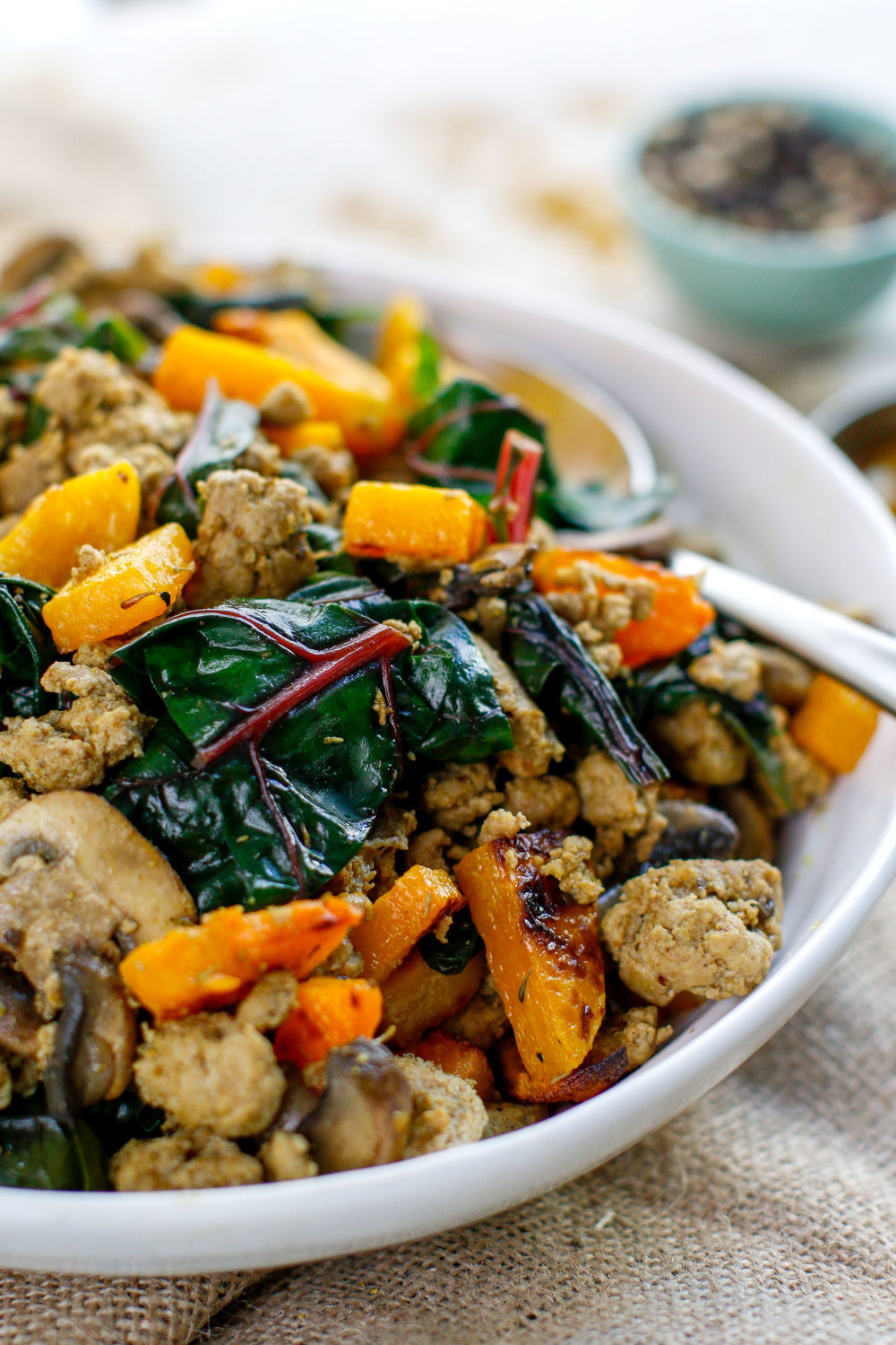A healthy turkey breakfast butternut bowl filled with maple turkey and sautéed chard and mushrooms. Seasoned with an Ayurvedic spice blend and a hint of maple syrup—think, maple turkey sausage! #butternut #breakfast #healthy