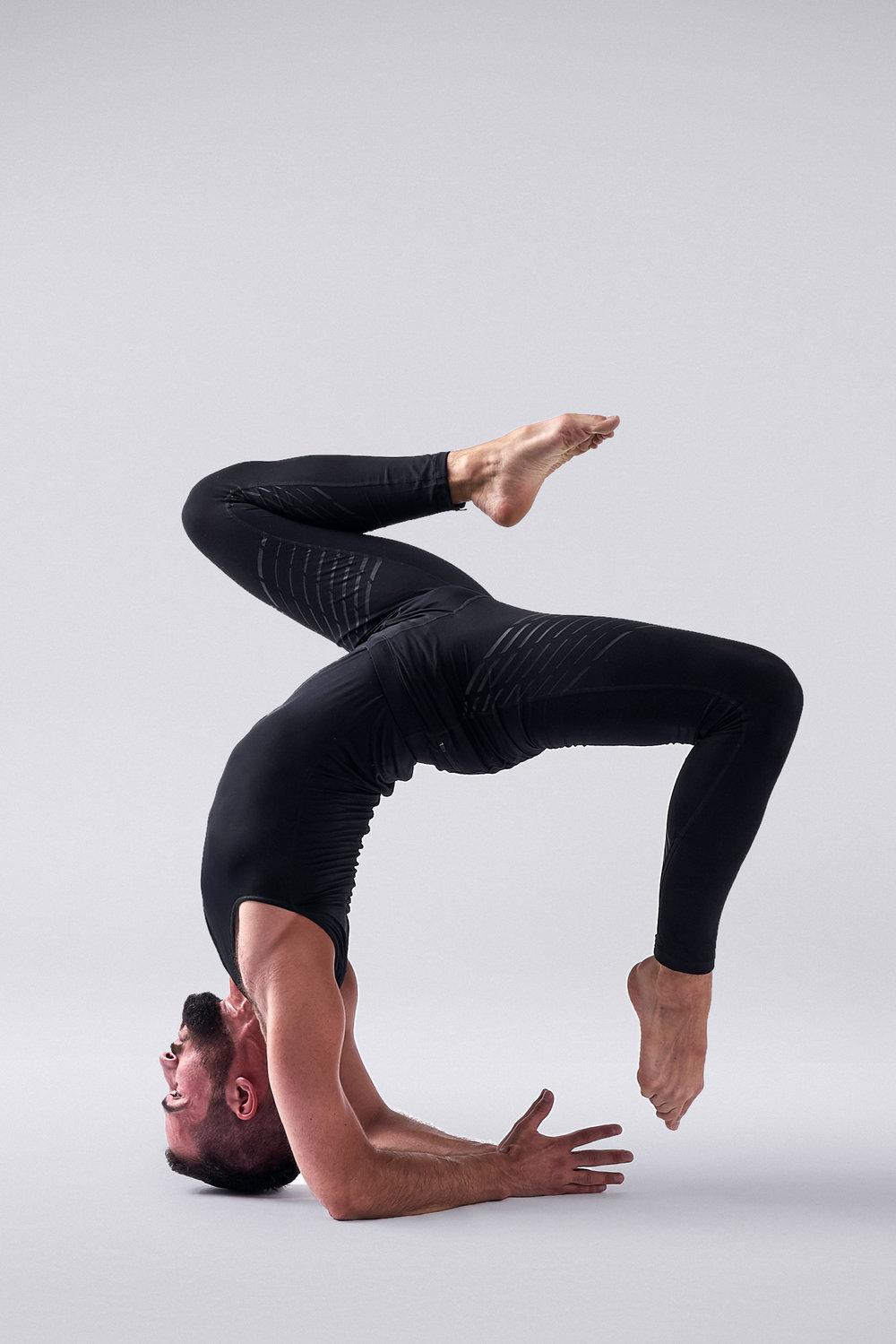 Man doing hollowback pincha forearm balance in leggings