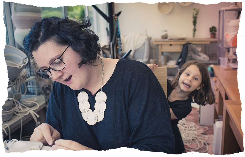 Jess Geach working in her home studio with her daughter. Image Viola Depcik.