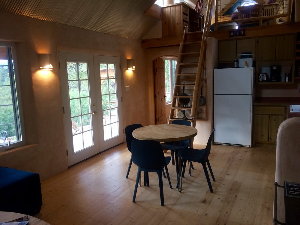 Bare Cottage kitchen and dining area with view of loft. Loft has queen size futon mattress and TV with DVD usage only