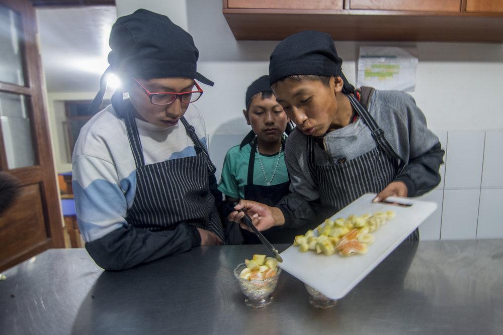 Los niños aprenden nuevas habilidades en la cocina del albergue.