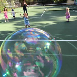 bubbles on tennis court with kids