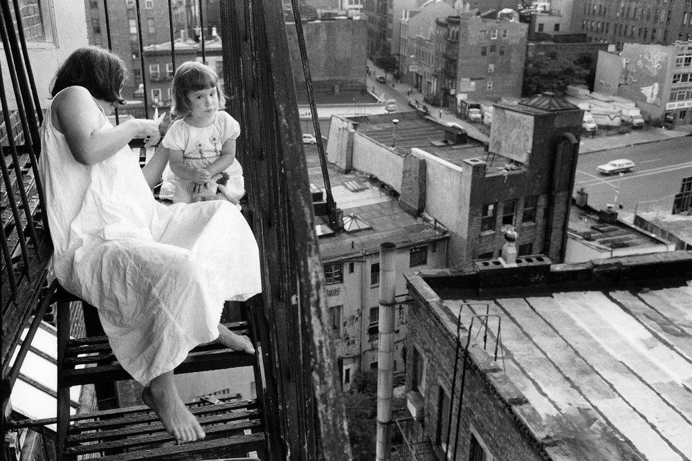 Third Street, New York City—Mary Ann cutting Eve's hair - 35mm black and white negative, 1984, © Geoffrey Biddle
