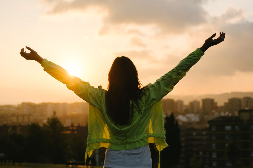 33530453 - back view of a blissful woman celebrating sport and fitness lifestyle success. female athlete raising arms to the sky after exercising for relax towards beautiful sunset or morning over city skyline.