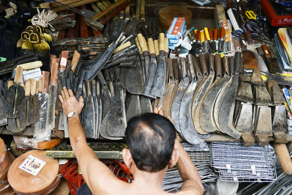A man inspects machetes and other tools March 1, 2013 at a street market in Kampot, Cambodia.