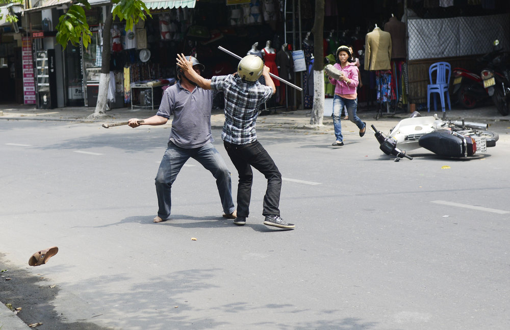A tailor, left, loses his sandal while fighting a competing tailor with a hammer in the streets of Hoi An, Vietnam on March 14, 2013.