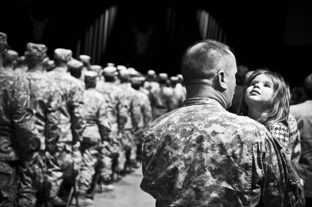 Sgt. 1st Class Rich Kemp, right, holds his daughter Erica during the National Guard's 34th Red Bull Infantry Division Departure Ceremony held at Roy Wilkins Auditorium in St. Paul on February 10, 2009.