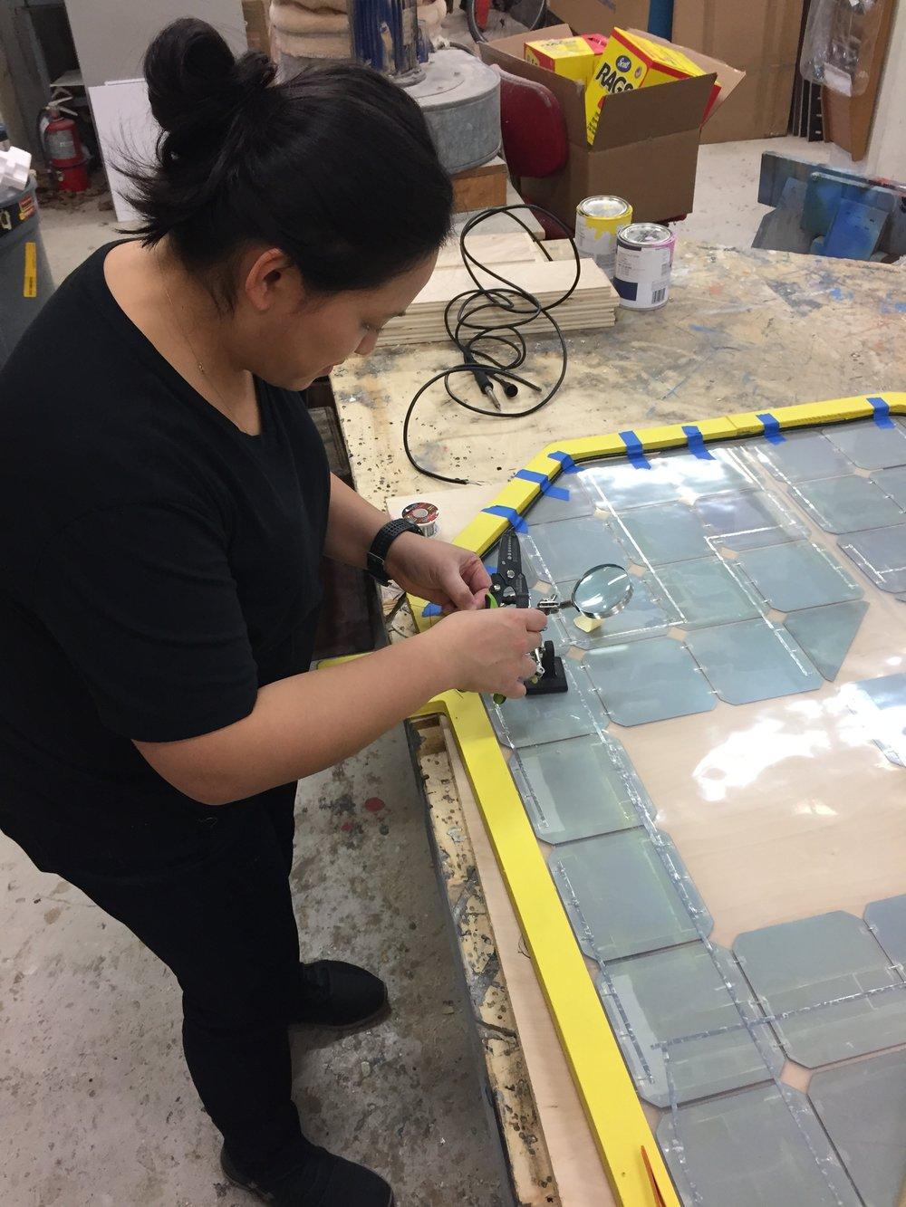 Collaborator Kristin Salomon soldering together the Solar Cat's panels