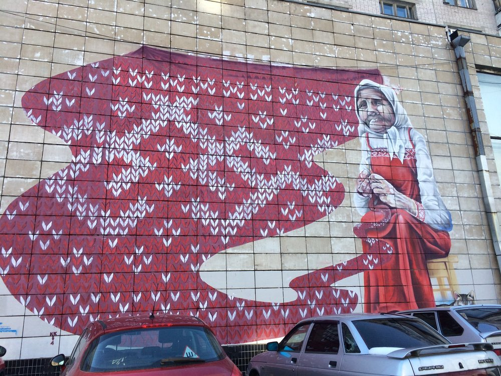 An amazing mural in Arkhangelsk depicting a grandmother doing her weaving with the pattern typical of this region.