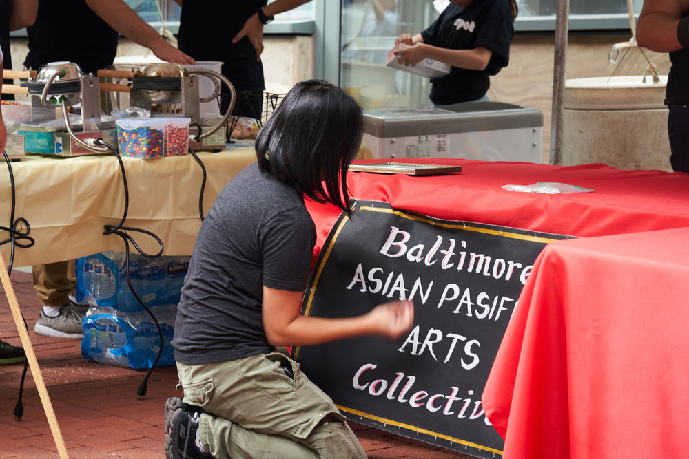 Staff member Mandy Yu fixing our table sign.    Photo courtesy of Daniel Ahn.