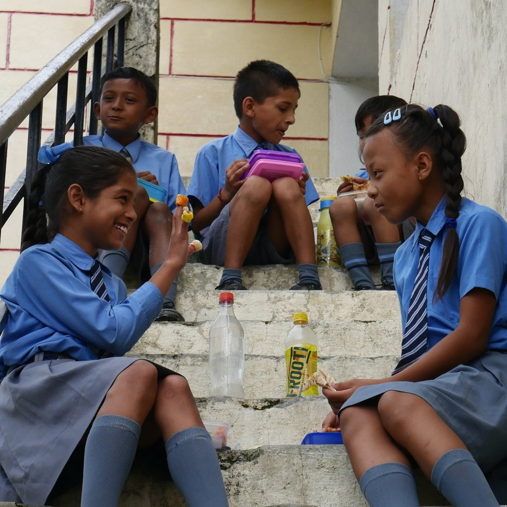 Fourth and fifth grade students at the Galaxy Public School enjoying lunchtime. They bring delicious traditional foods along with Frooti mango drink.