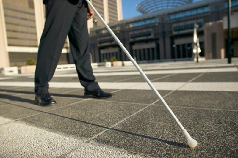 Man with visual impairments walking with his cane.
