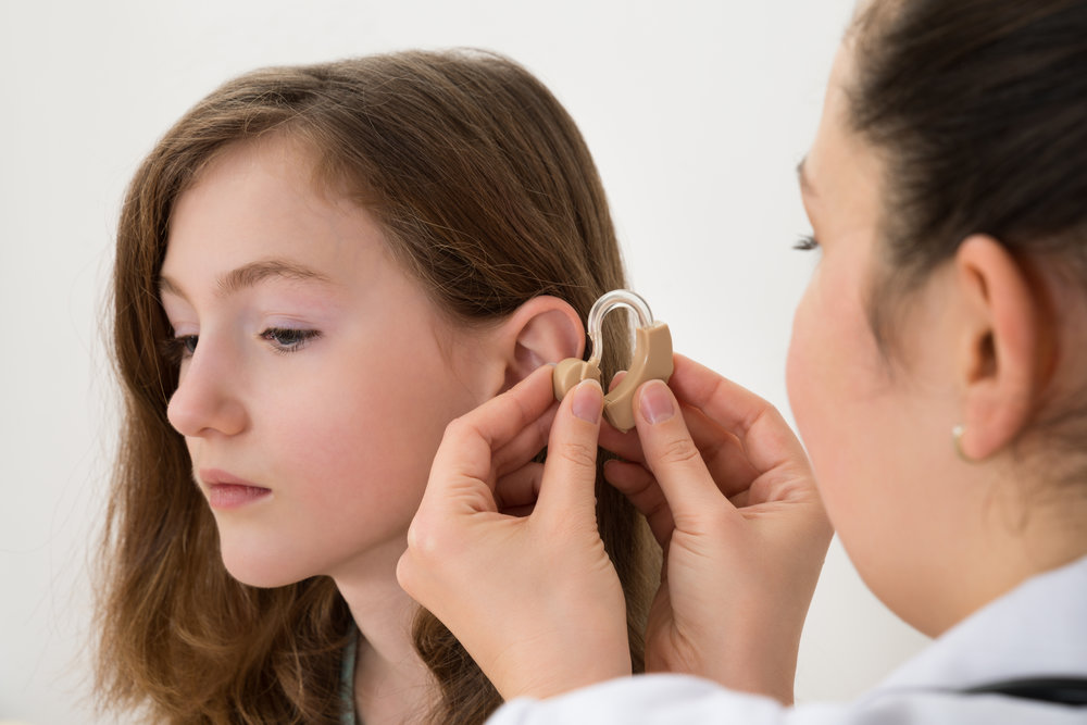 Woman assisting a young lady with a hearing impairment with her hearing aid.