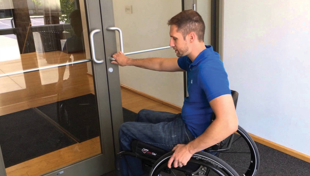 Photo Caption: A man in a wheelchair opening a traditional commercial grade manual door.