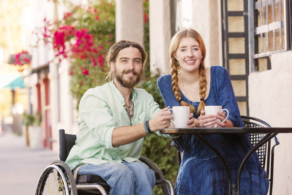 Photo Caption: Two people sitting at a table that is wheelchair accessible.
