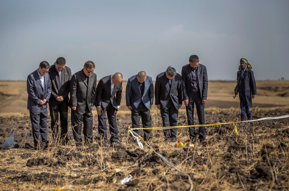 Chinese aviation officials prayed next to an offering of fruit, bread rolls and injera, an Ethiopian flatbread, at the crash scene on Tuesday.CreditMulugeta Ayene/Associated Press