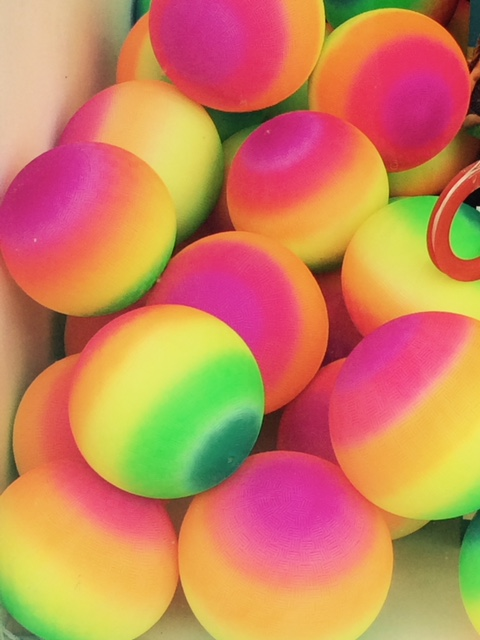 Image Description: close up photograph of very brightly coloured balls in electric shades of pink, yellow, green and orange.