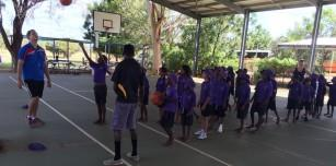 Jarrah Phillips (left) and Tristan McCarthy (right) run a basketball shooting drill with the girls and boys from Bayulu Community School.