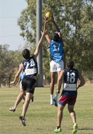 East Kimberley player Heze McCorry takes a mark in front of West Kimberley player John Davies.
