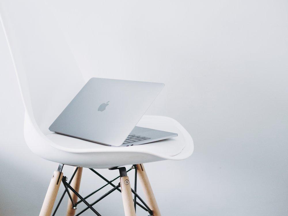 Apple MacBook on a white stool