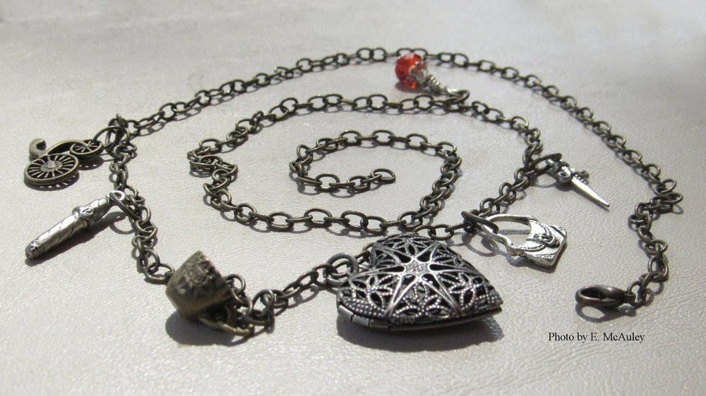 Bookish Crafts - One of my hobbies is making jewelry. Most of what I make is chainmail or steampunk, and I occasionally sell some of it at fairs and craft shows with artist friends.For every book I write, I make a special necklace with charms themed to the characters. Each hero and heroine gets 3-4 items to represent them, though sometimes tracking down the right sort of charms can be difficult. Each chain is anchored by a heart to symbolize their Happily Ever After.