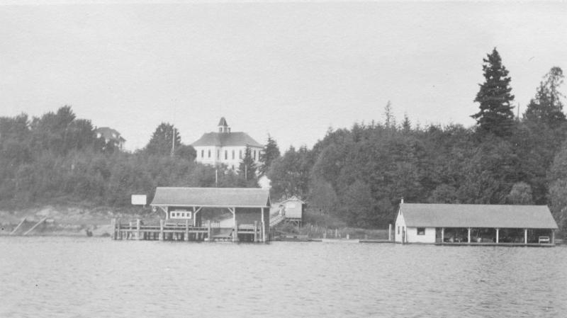 View from 1908, looking north across the early passenger ferry wharf to the Bellevue School on the hill--at the corner of Main and 100th Avenue today.